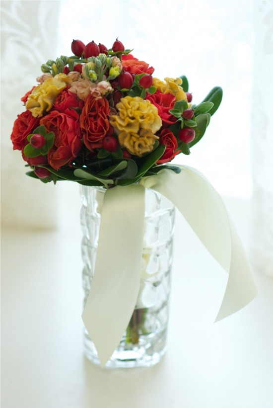 red and yellow wedding bouquet in windowsill