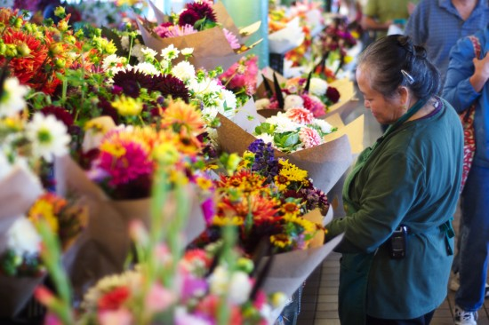 Old woman arranging flowers at Pike Place Market.