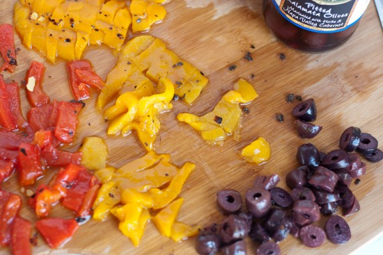 sliced roasted red and yellow peppers and olives for chickpea salad