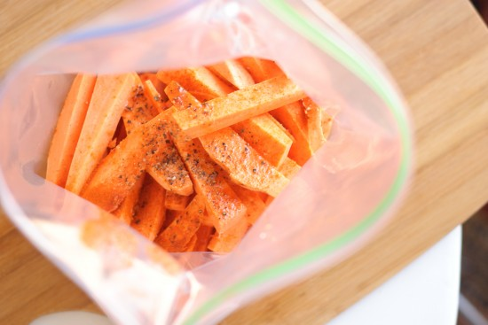 sweet potatoes, olive oil and spices in plastic bag