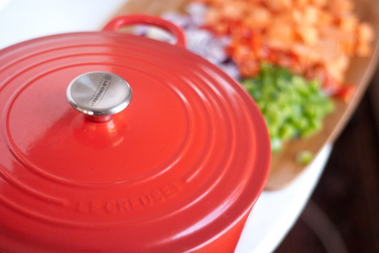 Red Le Creuset French oven and chili ingredients