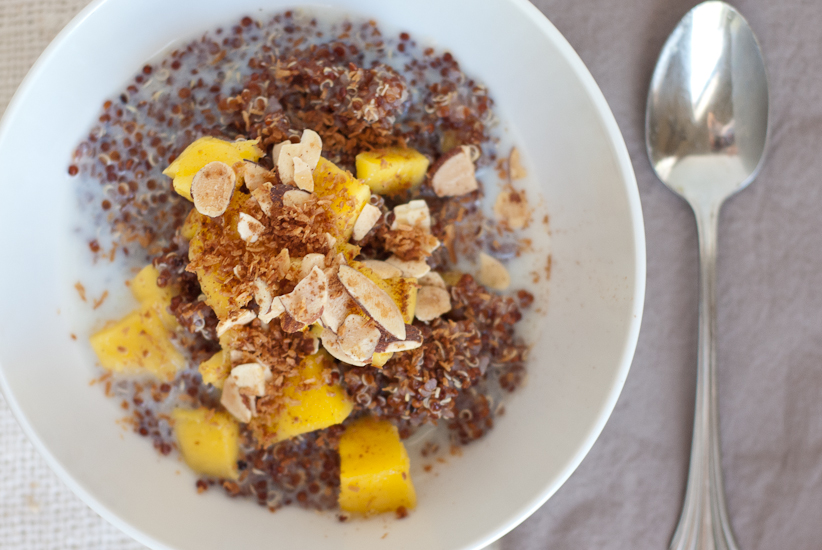breakfast quinoa with fresh mango, apple sauce, coconut and almonds