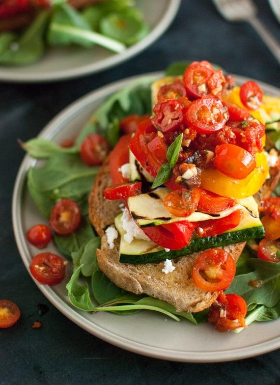 Ensalada de tomate apilado, verduras de verano y pan a la parrilla