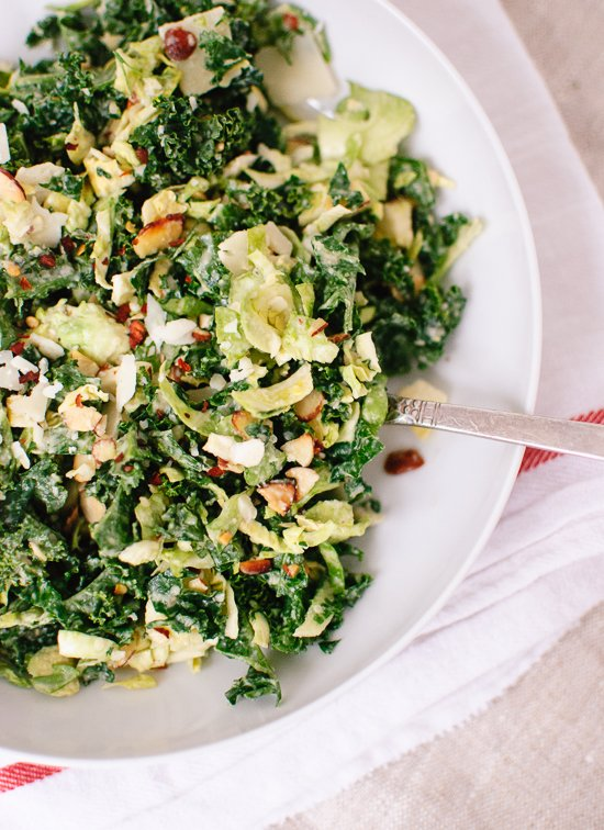 Raw kale and brussels sprouts salad with tahini-maple dressing and toasted almonds