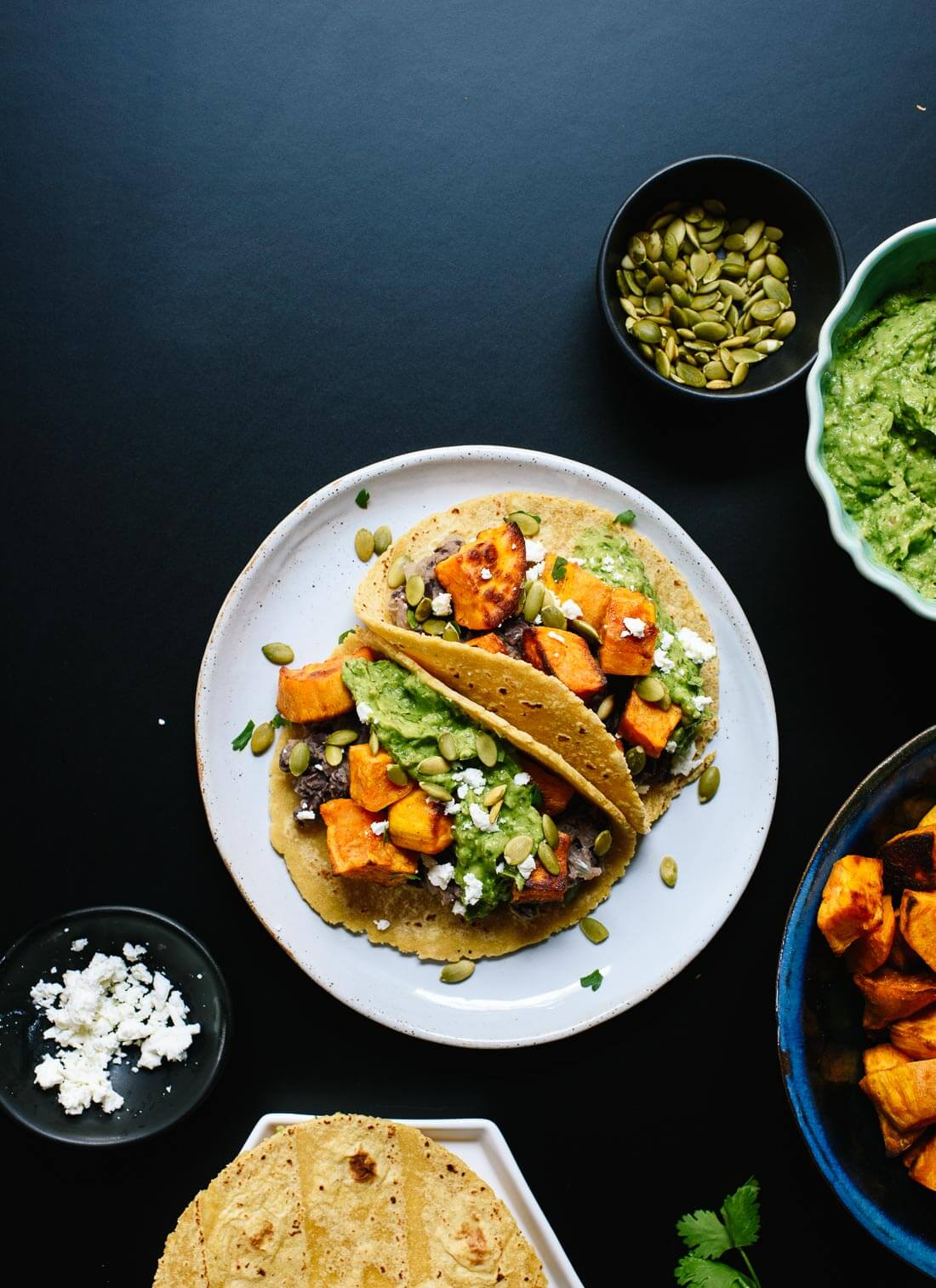 Delicious black bean and sweet potato tacos with avocado sauce and feta on top! Everyone loves these vegetarian tacos. cookieandkate.com
