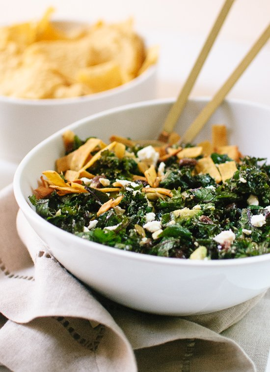 Hearty kale taco salad with feta, black beans, pepitas, avocado and tortilla strips, tossed in a spicy lime dressing - cookieandkate.com