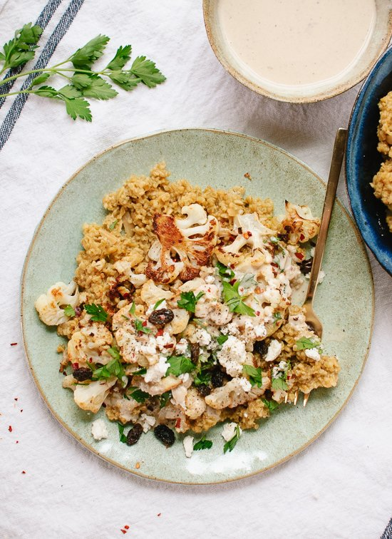 My new favorite meal: roasted cauliflower on a bed of healthy cracked freekeh pilaf, topped with tahini sauce, fresh parsley and raisins! cookieandkate.com