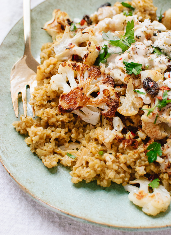 Roasted cauliflower on a bed of cracked freekeh, topped with an irresistible tahini sauce, fresh parsley and raisins - cookieandkate.com