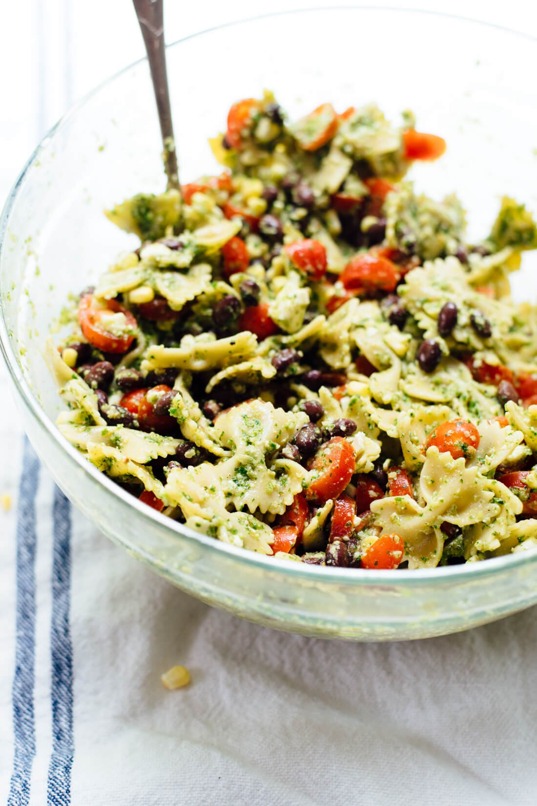 Healthy summer pasta salad with tomatoes, corn, black beans and a bold herbed pesto