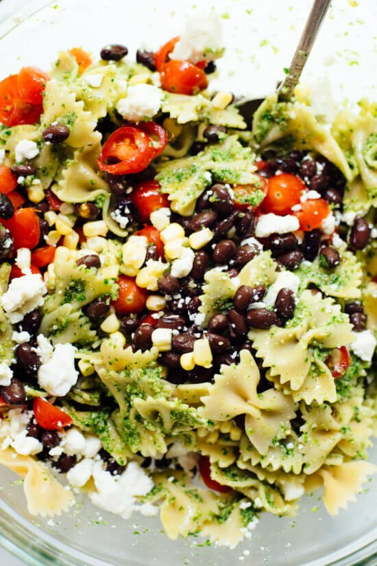Healthy summertime pasta salad, made with jalapeño-cilantro pesto, cherry tomatoes, corn, black beans and feta. You'll love this surprising combination!