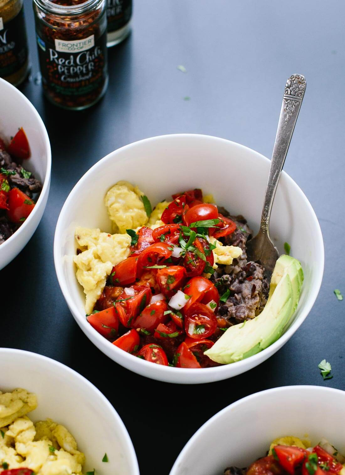 Delicious breakfast bowls made with scrambled eggs, black beans, pico de gallo and sliced avocado! cookieandkate.com