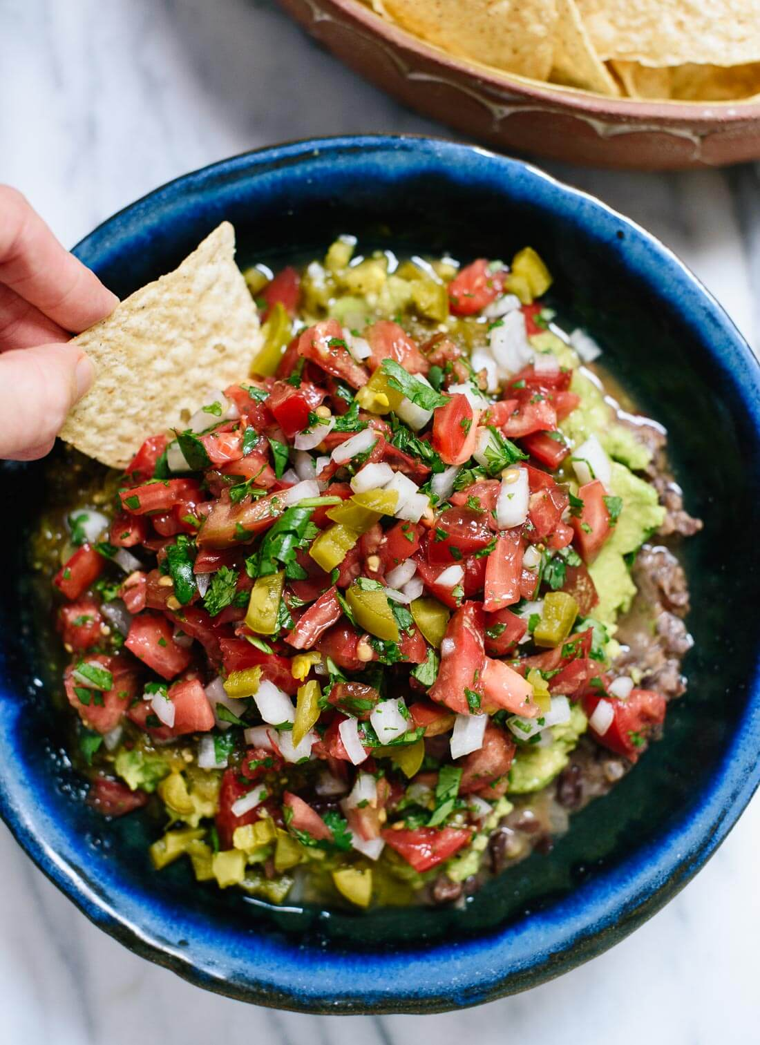 "This 7 layer dip recipe features layers of freshly prepared ""refried"" black beans, guacamole, salsa and pico de gallo! cookieandkate.com"