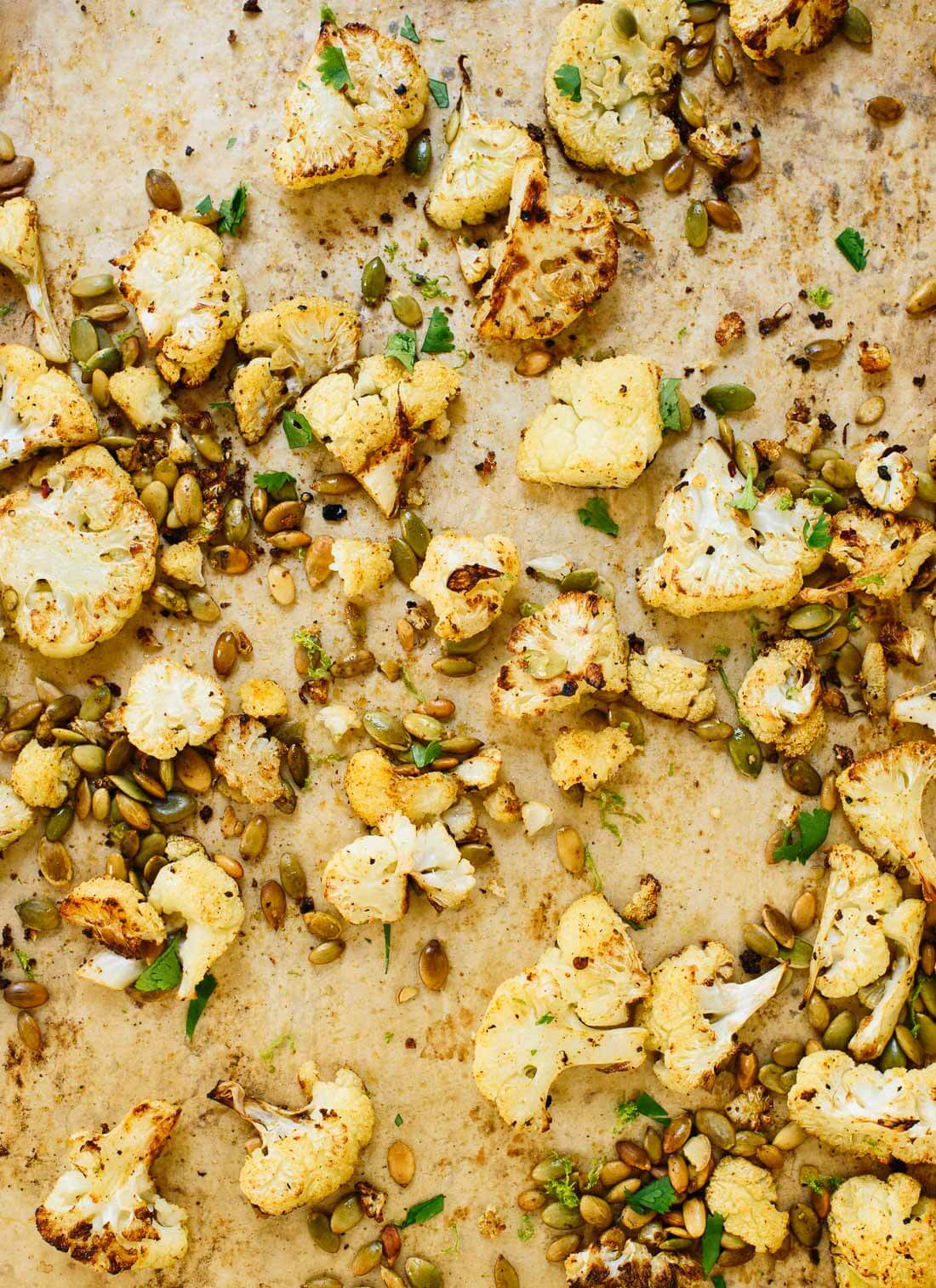 Roasted cauliflower with Mexican flavors (cumin, chili powder, pepitas and lime!). It's the perfect healthy side dish for your favorite Mexican recipes! cookieandkate.com
