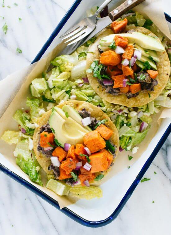 "This vegetarian tostadas recipe features roasted sweet potatoes and healthy ""refried"" black beans, served on a crisp salad. Gluten free and easily vegan!"