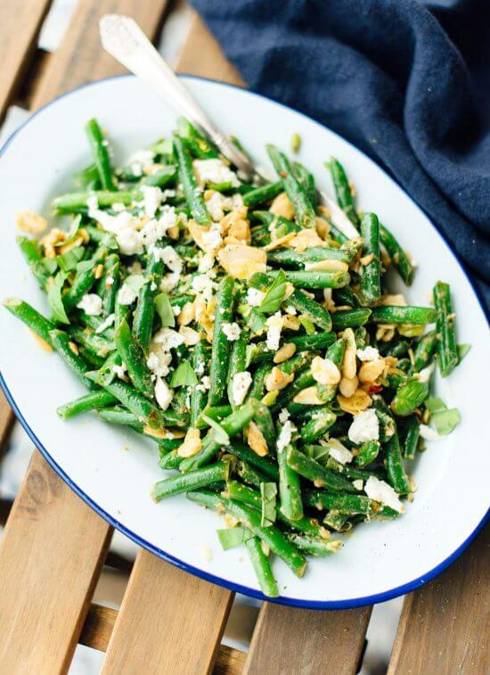 Green bean salad recipe featuring toasted almonds and feta, tossed in an irresistible lemon-garlic sauce. cookieandkate.com