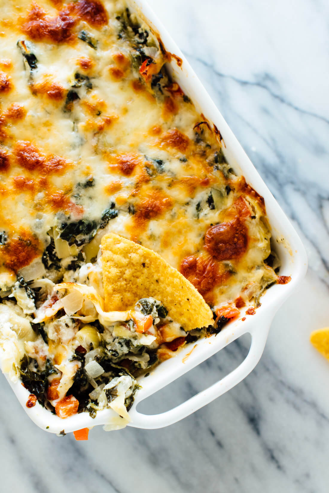 The best cheesy baked spinach artichoke dip, made lighter with extra veggies and no mayonnaise! Everyone will love this appetizer recipe.