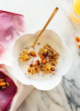 Orange almond granola in cereal bowl with milk