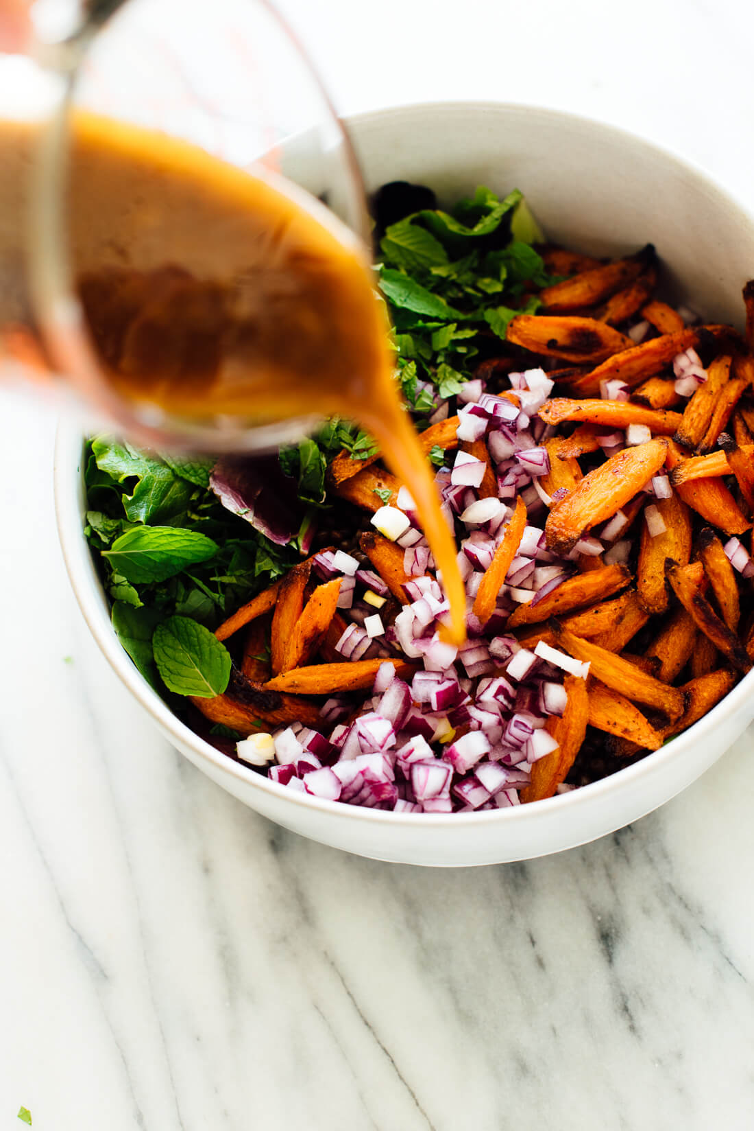 pouring salad dressing onto masala lentil salad
