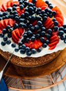 slicing lemon almond cake with berries on top-4