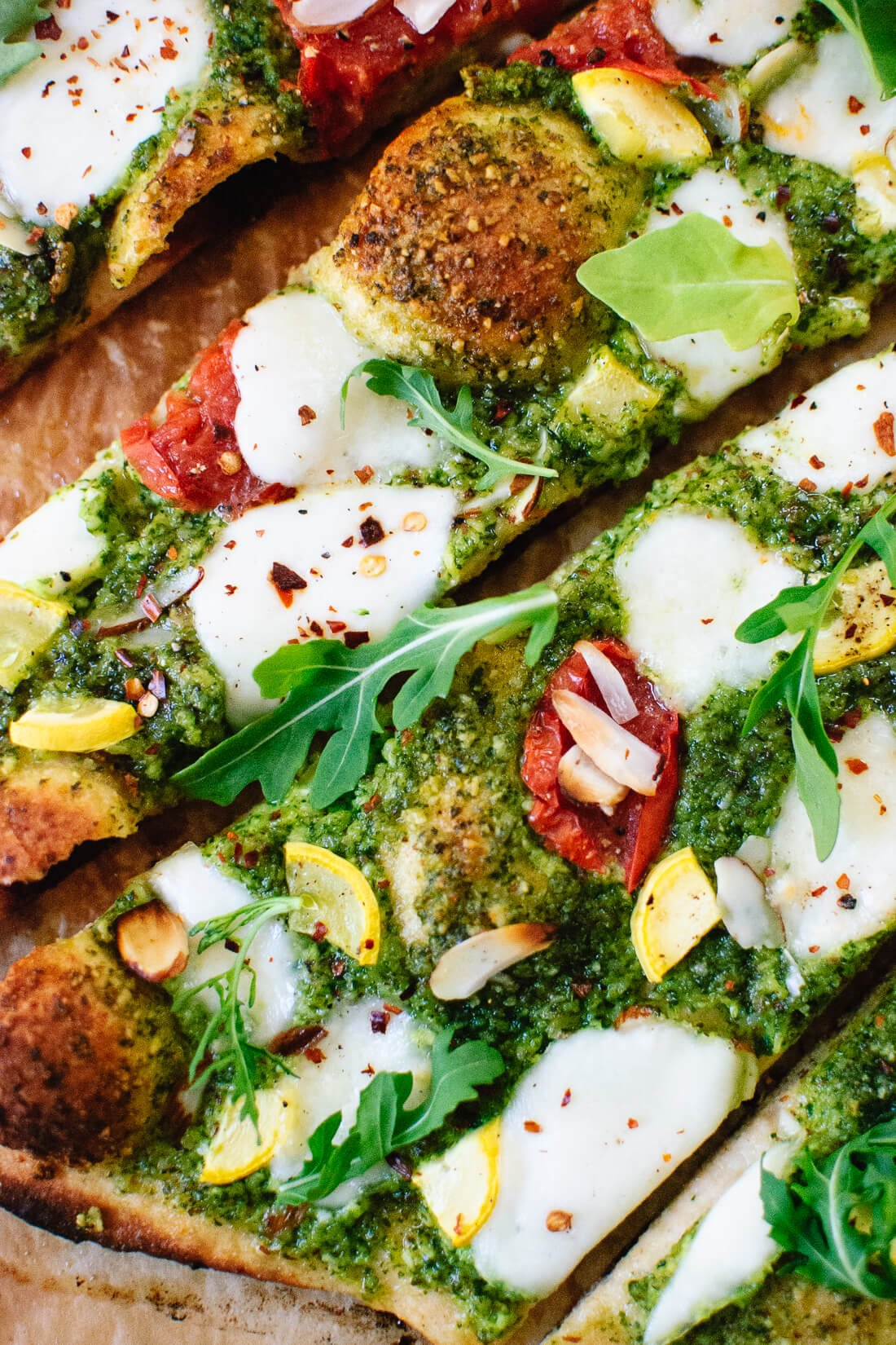 Summertime arugula-almond pesto pizza with a simple whole wheat crust