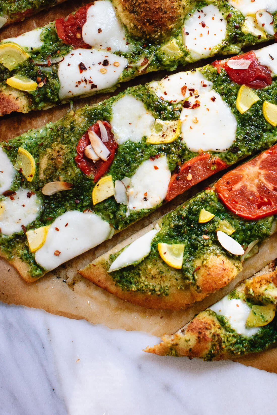 Homemade arugula-almond pesto pizza with a simple whole wheat crust