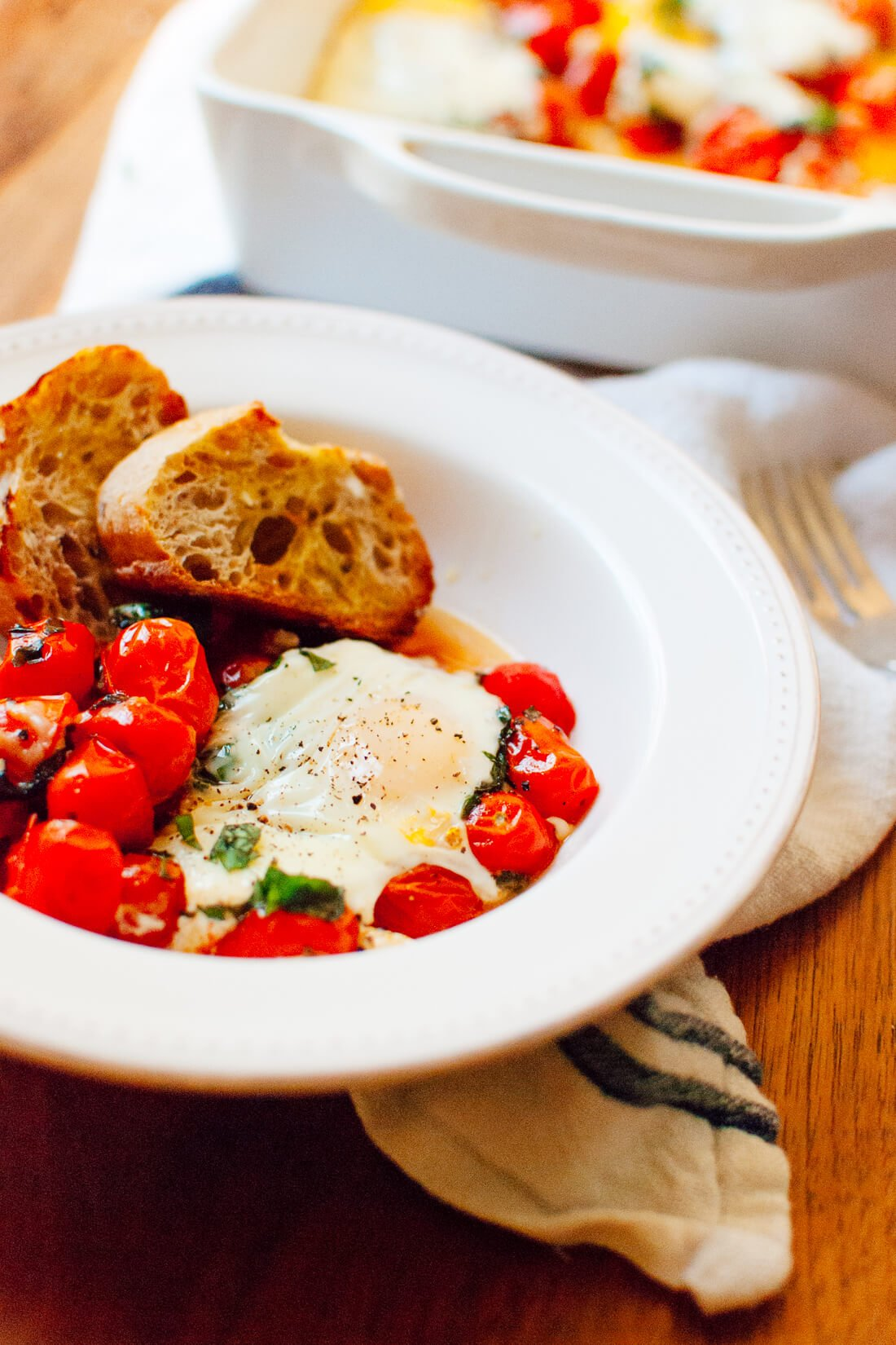 Baked Eggs on a Bed of Roasted Cherry Tomatoes in bowl
