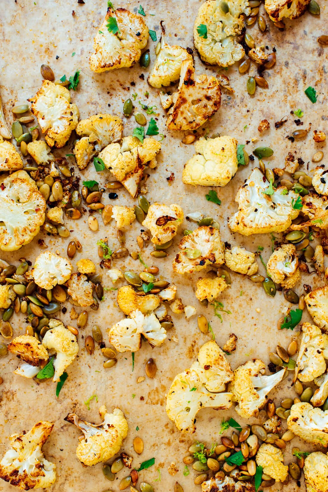 Roasted cauliflower with Mexican flavors (cumin, chili powder, pepitas and lime!). It's the perfect healthy side dish for your favorite Mexican recipes!