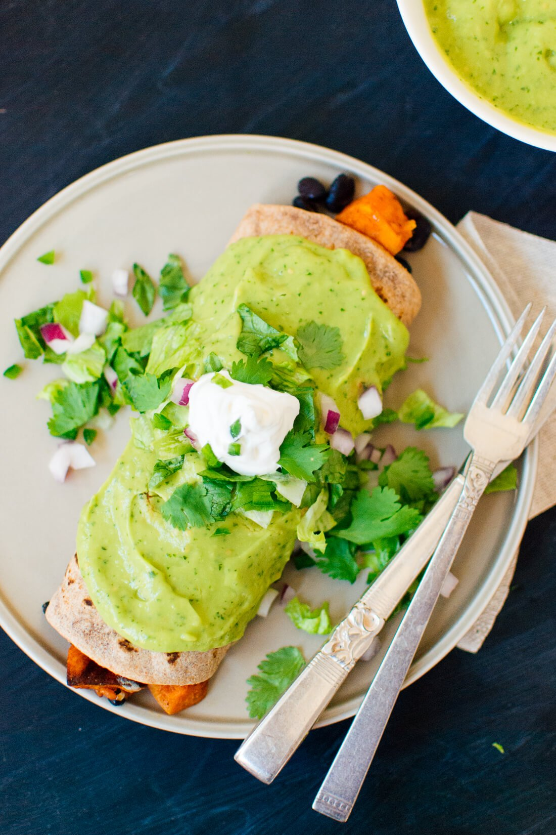 Sweet potato burrito with avocado sauce and sour cream