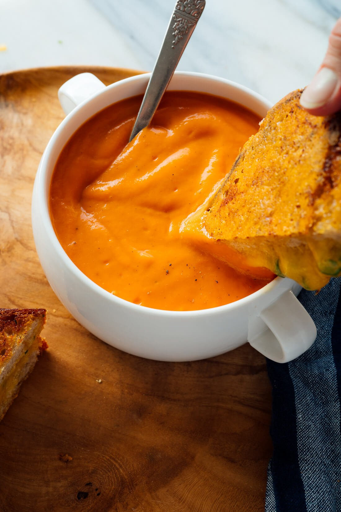 grilled cheese dipping into tomato soup