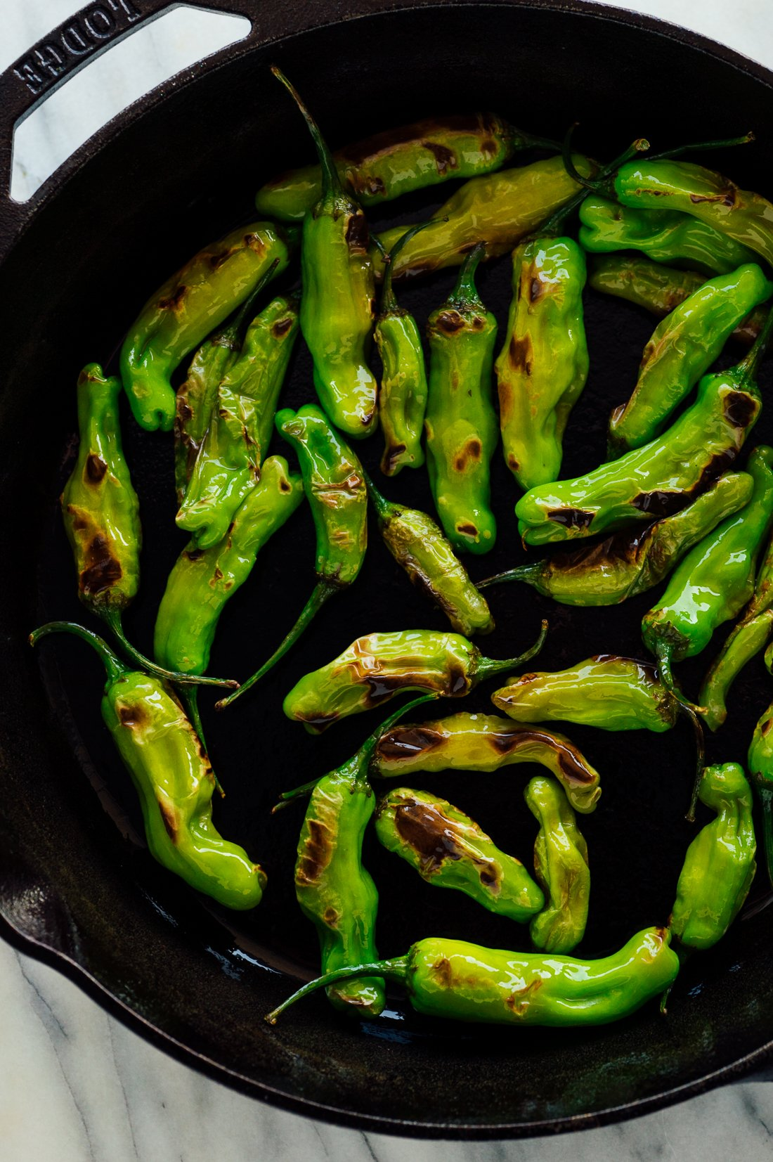 blistered shishito peppers in skillet