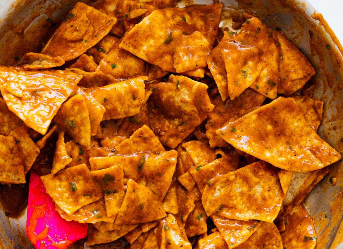 tortilla chips tossed in red enchilada sauce
