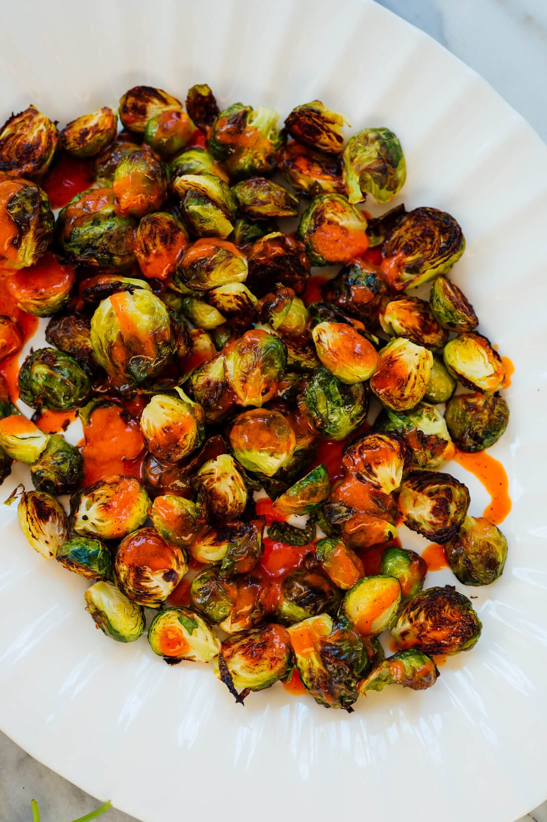 Buffalo sauce drizzled on Brussels sprouts
